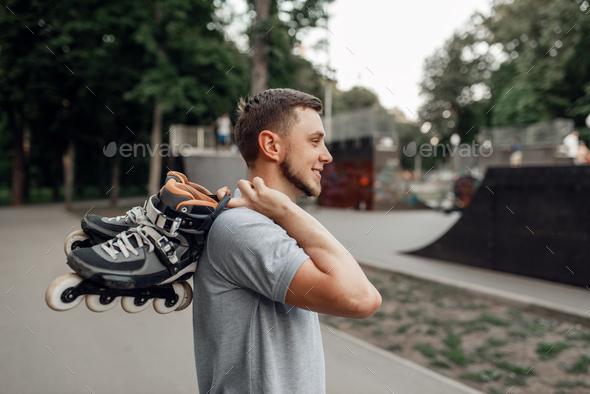 Roller skating, skater carries skates on shoulder - Stock Photo - Images