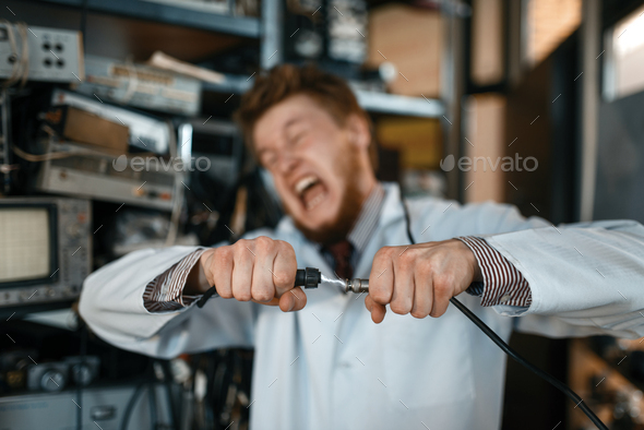 Engineer connects wires under tension in lab - Stock Photo - Images