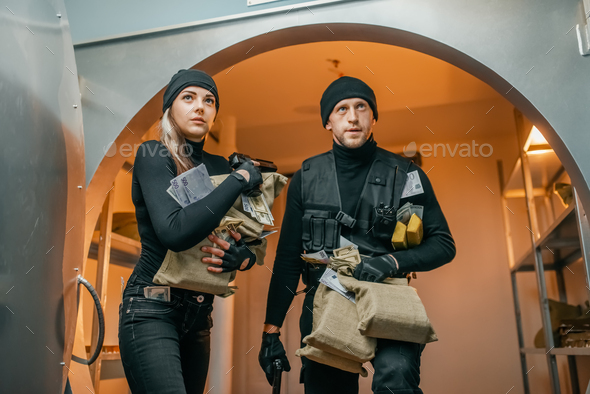 Two robbers with money left the vault - Stock Photo - Images