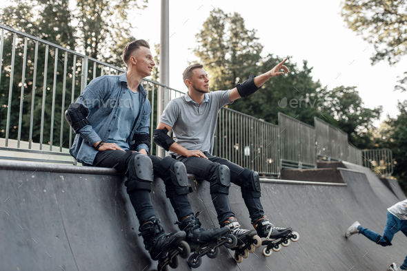 Roller skating, two skaters sitting on the ramp - Stock Photo - Images