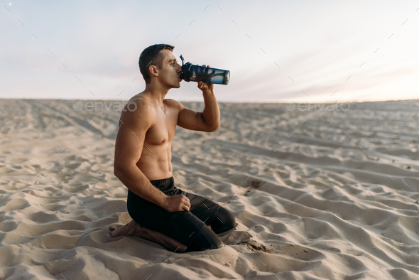 Male athlete drinks water after workout in desert - Stock Photo - Images