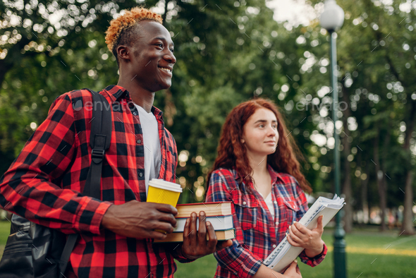 Two students walk on the sidewalk in summer park - Stock Photo - Images