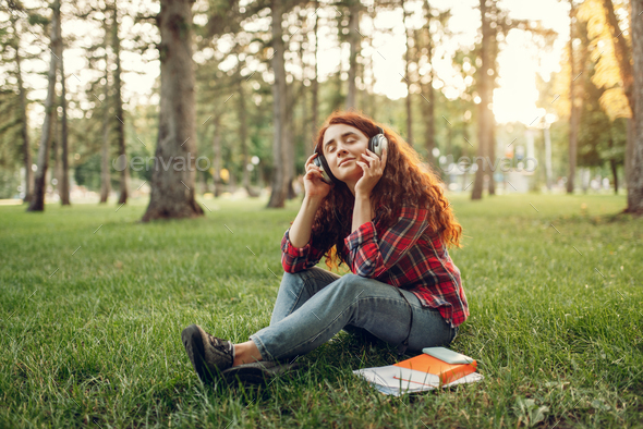 Female student in headphones sitting on the grass - Stock Photo - Images