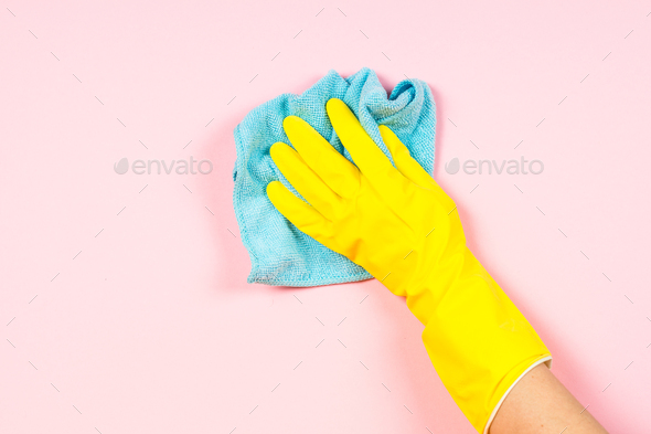 Hand in yellow gloves and microfiber rag cleaning pink background - Stock Photo - Images