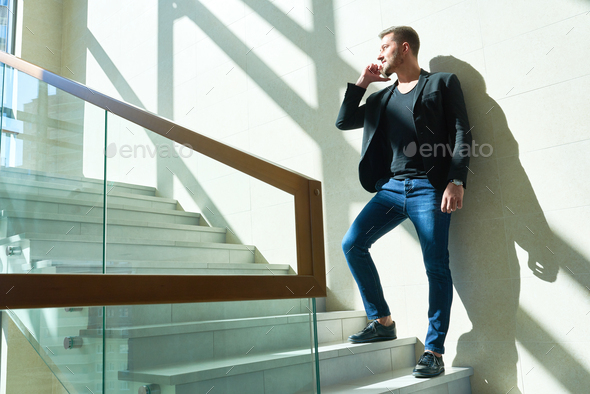 Handsome Man Speaking by Phone Indoors - Stock Photo - Images