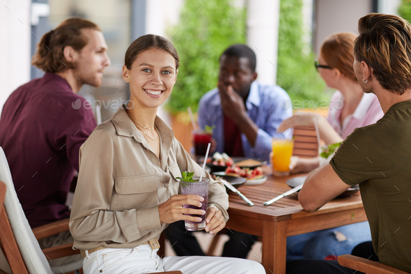 Smiling Woman Enjoying Lunch with Friends in Cafe - Stock Photo - Images