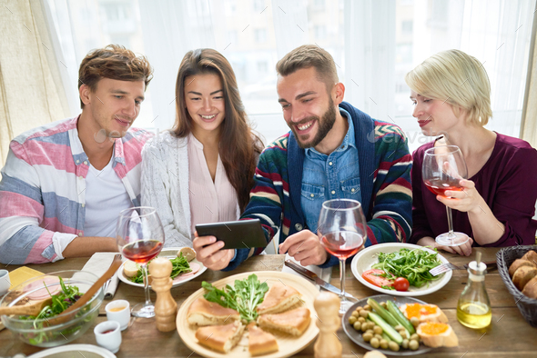 Friends Watching Video at Dinner Table - Stock Photo - Images
