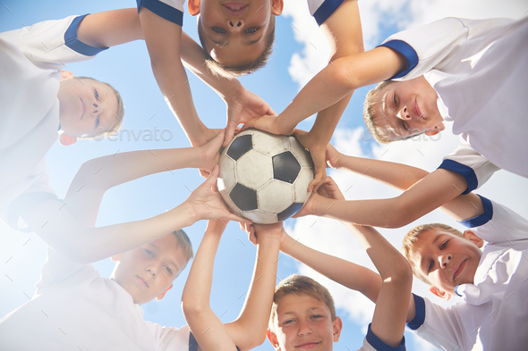 Happy Junior Football Team Holding Ball - Stock Photo - Images