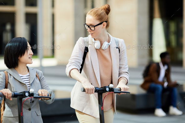 Girls Riding Scooters in City - Stock Photo - Images