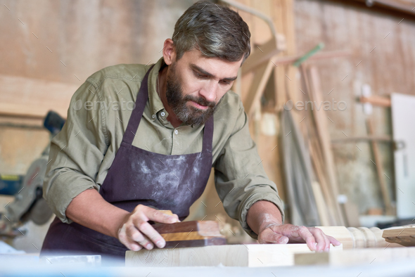 Bearded Carpenter Sanding Wood in Shop - Stock Photo - Images