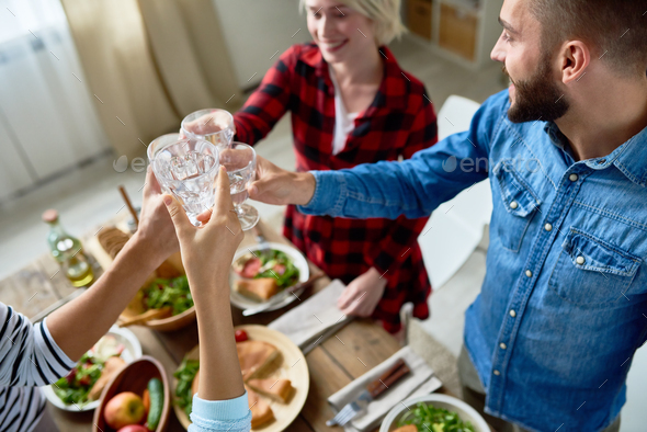 Friends Clinking Glasses at Thanksgiving Dinner - Stock Photo - Images