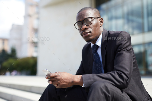 African-American Businessman Sitting on Steps - Stock Photo - Images