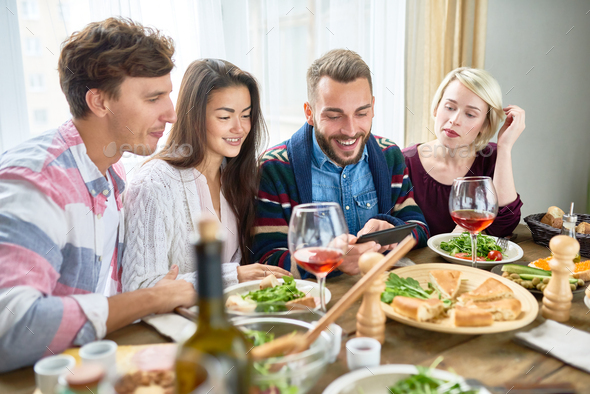 Young People Watching Videos at Dinner Table - Stock Photo - Images