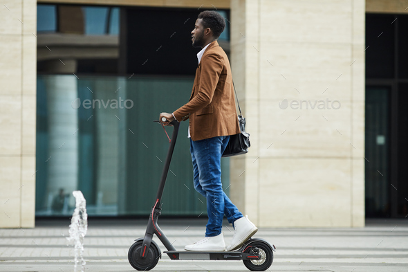 African Man Riding Electric Scooter Background - Stock Photo - Images