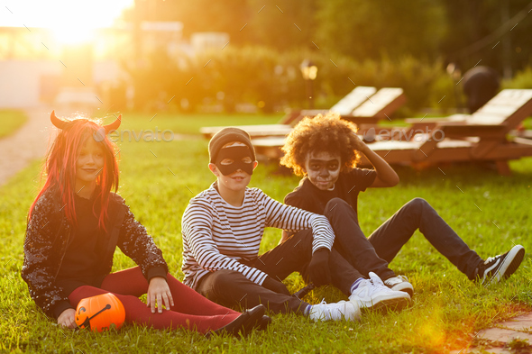 Friends Sitting on Grass on Halloween Day - Stock Photo - Images