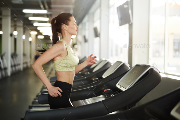 Woman Running on Treadmill in Gym - Stock Photo - Images