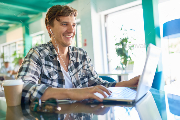 Happy Young Man Working with Laptop in Office - Stock Photo - Images