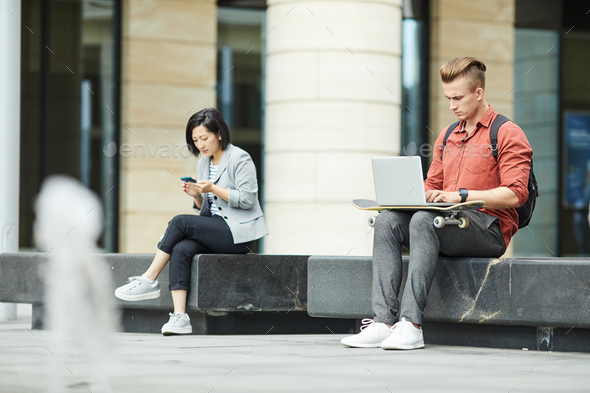 Young People Using Electronic Devices in City - Stock Photo - Images