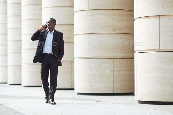 African-American Businessman walking in City - Stock Photo - Images