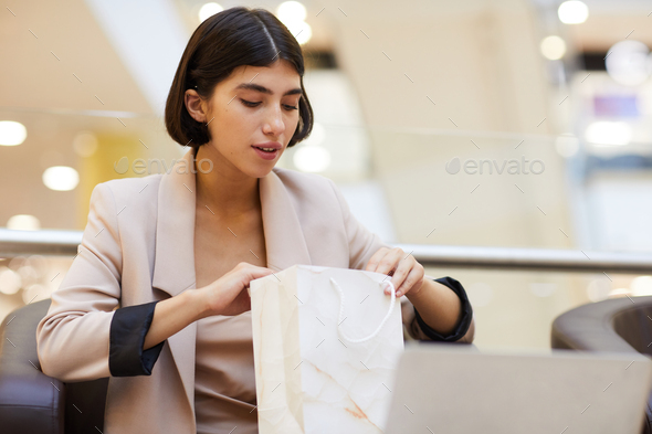 Beautiful Woman Looking in Shopping Bag - Stock Photo - Images