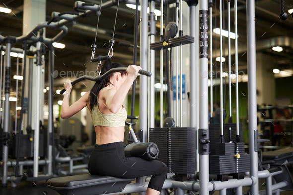 Fit Woman using Exercise Machines in Gym - Stock Photo - Images