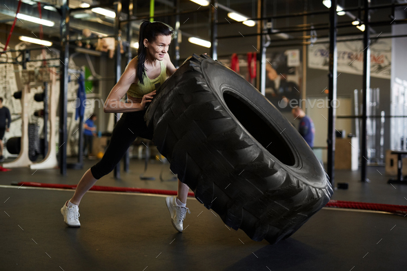 Woman Flipping Truck Tire in Gym - Stock Photo - Images