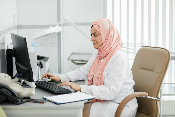 Middle-Eastern female Doctor at desk - Stock Photo - Images