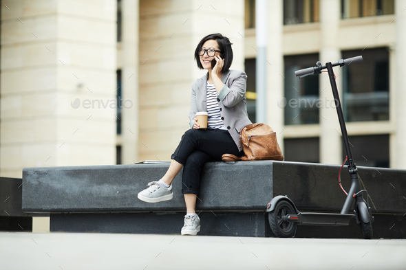 Modern Asian Woman Speaking by Smartphone Outdoors - Stock Photo - Images
