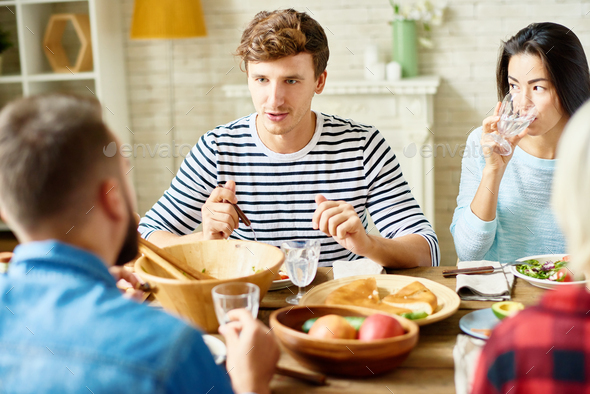 Young Man at Dinner with Friends - Stock Photo - Images