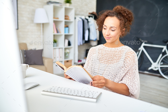 Mixed-Race Woman Relaxing at Desk in Home Office - Stock Photo - Images