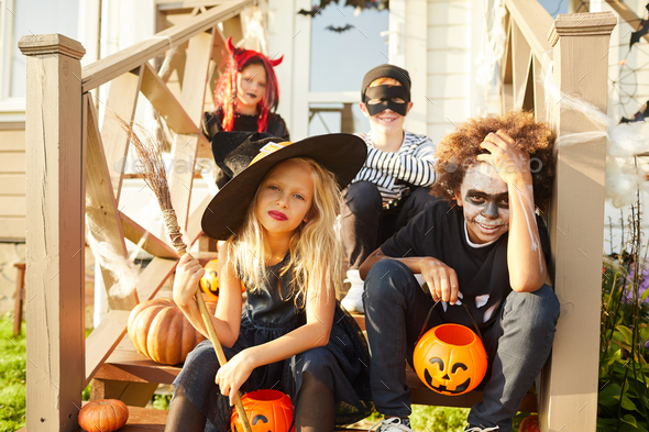 Kids Sitting on Porch on Halloween - Stock Photo - Images
