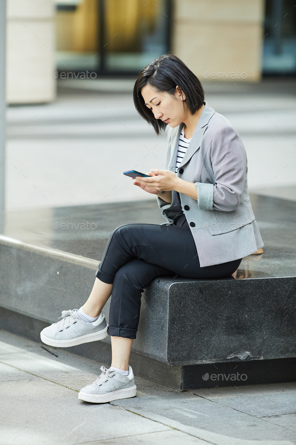 Modern Asian Woman using Smartphone in City - Stock Photo - Images