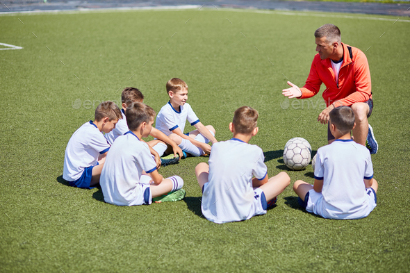 Coach Instructing  Football Team in Field - Stock Photo - Images