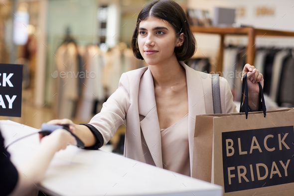 Young Woman Buying Clothes in Boutique - Stock Photo - Images