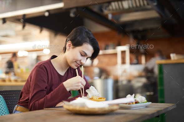 Young Woman Enjoying Asian Food in Cafe - Stock Photo - Images