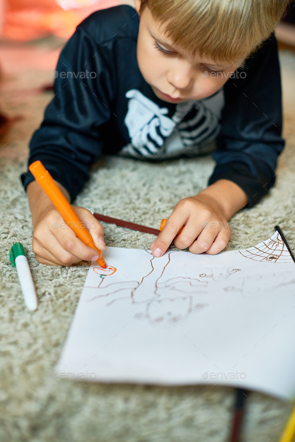 Little Boy Drawing Pictures on Halloween - Stock Photo - Images