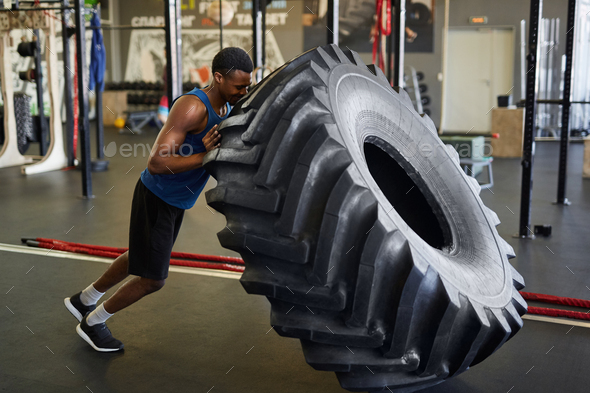 African Sportsman Flipping Tire in Gym - Stock Photo - Images