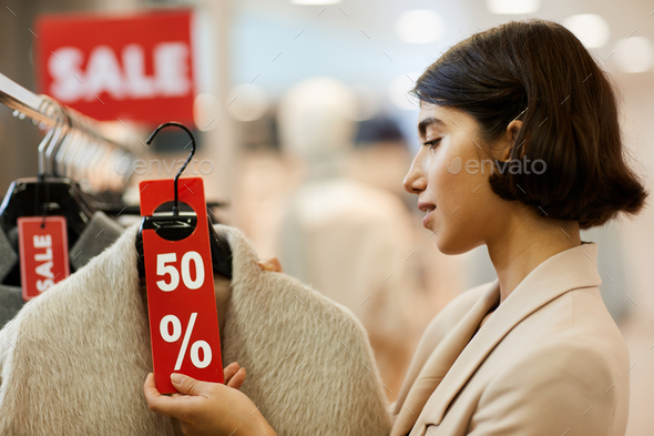 Young Woman Choosing Clothes on Sale - Stock Photo - Images