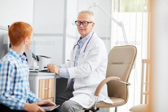 Senior Doctor Talking to Teenage Boy - Stock Photo - Images