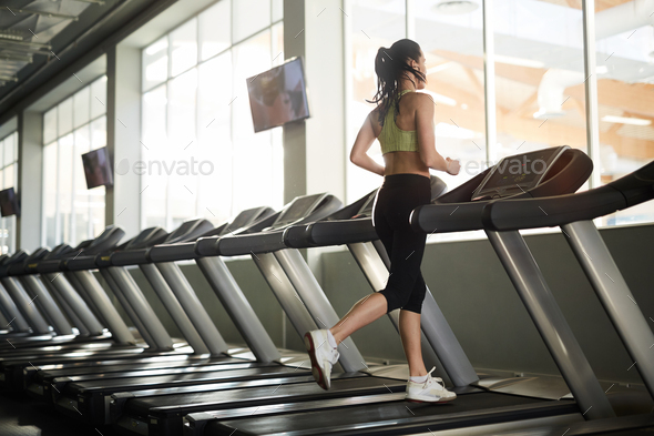Young Woman Running on Treadmill - Stock Photo - Images
