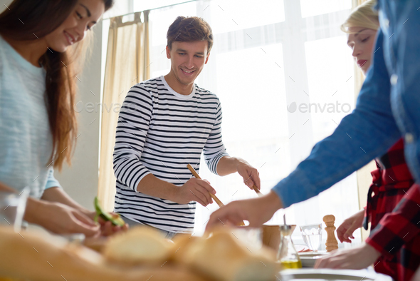 Young Man with Friends Setting Dinner Table - Stock Photo - Images