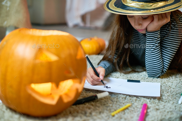 Cute Girl Drawing Halloween Pictures - Stock Photo - Images