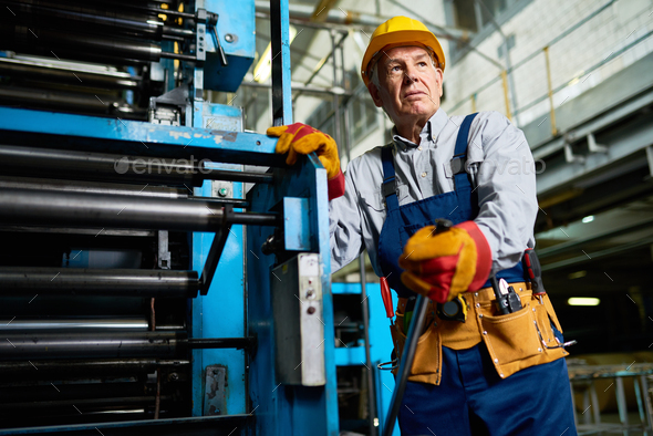 Senior Worker operating Machines at Factory - Stock Photo - Images