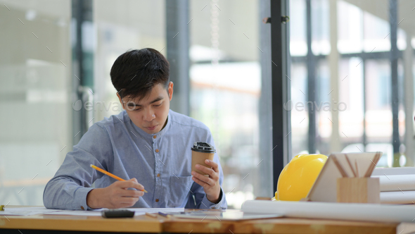 Engineering is checking floor plan in office.He held a pencil and coffee cup in hand and seriously. - Stock Photo - Images