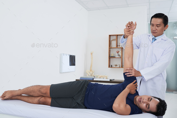 Physiotherapist checking arm - Stock Photo - Images