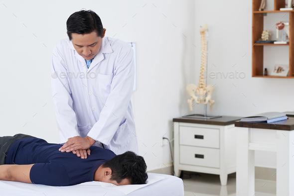 Chiropractor adjusting spine - Stock Photo - Images