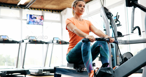 Young blonde woman working on rowing machine - Stock Photo - Images