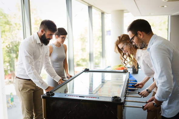 Coworkers playing table football on break from work - Stock Photo - Images