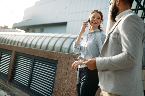 Business man and woman working outdoors with tablet computer in front of office - Stock Photo - Images