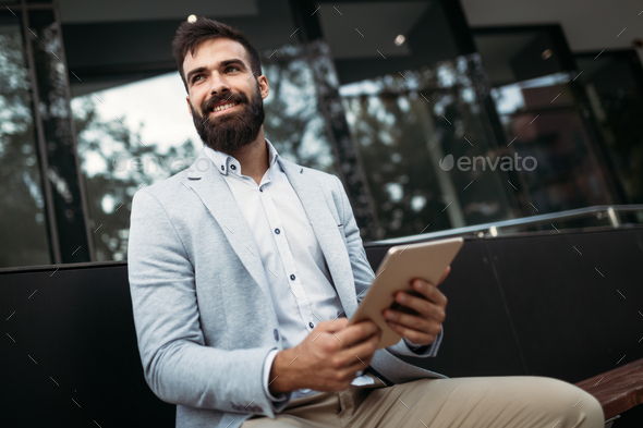 Shot of smiling businessman sitting on bench with digital tablet - Stock Photo - Images